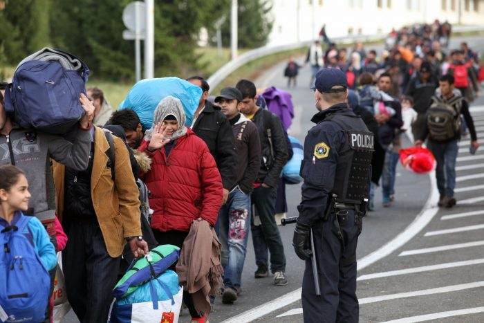 Sentilj, Slovenia - November 19, 2015: A group of refugees and migrants escorted by Slovenian police walk from the Slovenian to the Austrian transit camp on the border. The countries along the West Balkan route, including Slovenia, have now restricted access to refugees who can prove they are fleeing war, effectively meaning those from Syria, Afghanistan and Iraq.